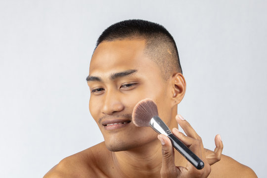 Men with makeup mustache, transform mascara, blush ,The guy with his face brushes the brush.Men make up the separate background.