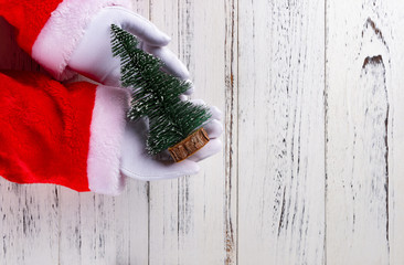santa claus holding a Christmas tree model on a white wood background