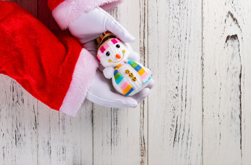 santa claus holding a snow man doll on hands