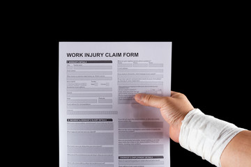 wrapped hand holding a work injury claim form