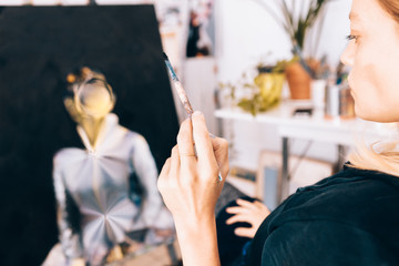close up of a female artist painter while holding a paintbrush
