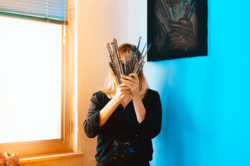 portrait of a female artist painter working in her studio atelier