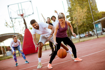 Group of multiethnic people  playing basketball on court Wall mural
