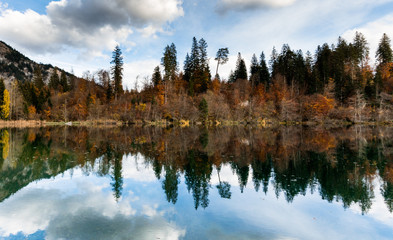 Wall Mural - the picturesque Cresta Lake in the mountains of Switzerland near Flims in the Grisons on a beautiful fall day with colorful foliage and trees and reflections