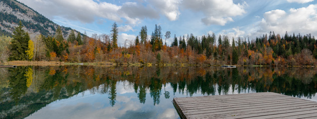 Wall Mural - fall color forest and foliage panorama landscape surround an idyllic mountain lake in the Alps of Switzerland on a late autumn day with reflections in the water with a wooden boardwalk in the foregrou