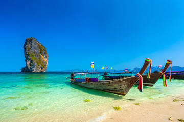 Wooden longtailed boats on a sandy beach in the crystal clear turquoise water of the Adaman Sea near the picturesque limestone rock island under a blue sky. Poda Island, AO Nang, Krabi, Thailand.