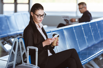 young businesswoman in glasses using smartphone at airport