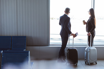 businessman and businesswoman looking at window at departure lounge in airport