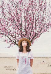 Teenage woman with bubble gum in blooming orchard