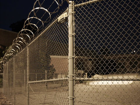 Close up of a chain link barbed wire fence in front of a yard at night
