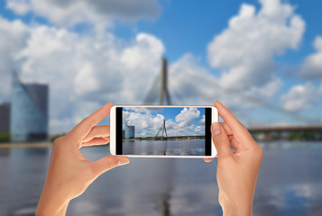 A tourist is taking a photo of cable-stayed bridge in Riga in summer sunny day on a mobile phone