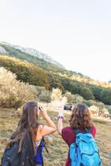 Traveling women on hillside in autumn