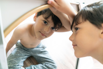 Boy looking at camera from mirror