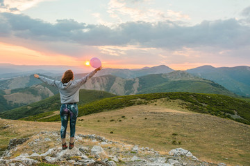 Woman with balloon standing in sunset mountains