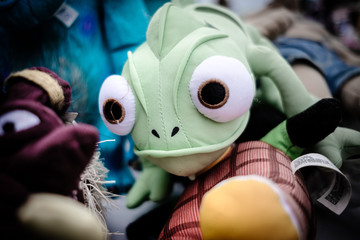 Green cuddly toy with big eyes on pile of toys