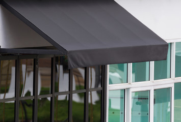black exterior awning over aluminium frame window of shop. sun light on black canvas shading.
