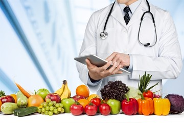 Young man doctor holding digital tablet on fruits and vegetables