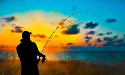 Silhouette of fishing man on coast of sunset sea