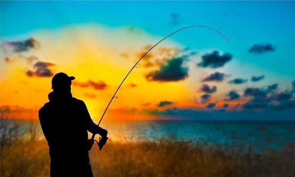 Silhouette of fishing man on coast of sunset sea