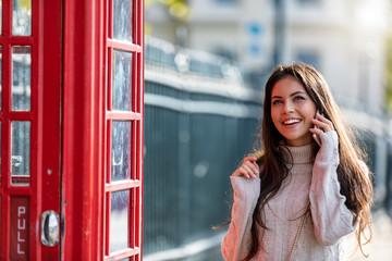 Attraktive Frau in London an einer roten Telefonzelle telefoniert mit ihrem Handy; Touristin in London beim Sightseeing