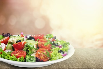 Wall Mural - Greek salad with fresh vegetables on background