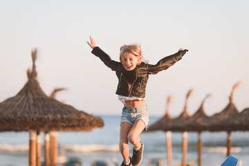 Young girl, primary school age,  wearing cool black leather jacket, jumping on the beach