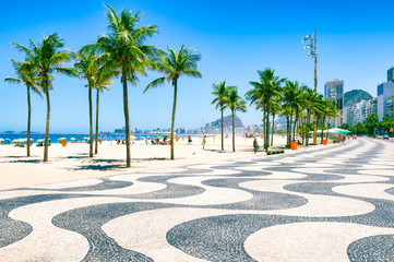 Poster Rio de Janeiro Bright morning view of the curving boardwalk tile pattern with palm trees at Copacabana Beach with the skyline of Rio de Janeiro, Brazil