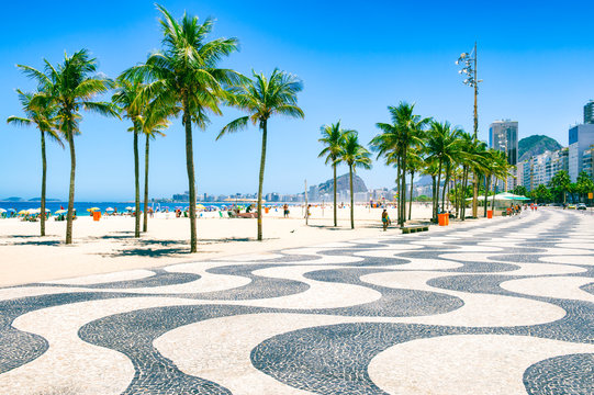 Bright morning view of the curving boardwalk tile pattern with palm trees at Copacabana Beach with the skyline of Rio de Janeiro, Brazil