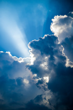 Heavenly light shining through billowing clouds in a stormy sky
