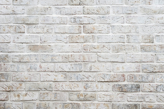 White painted brick wall full frame background with gritty textured imperfections