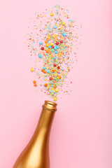 Champagne bottle with colorful sprinkles on pink background