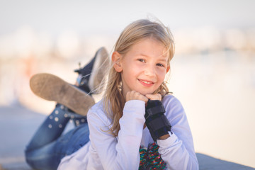 Young girl, primary school age, wearing removable wrist brace, lying on wall and smiling at camera