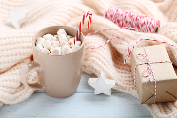 Cappuccino with marshmallows and gift box on wooden table