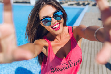 Close-up selfie-portrait of attractive brunette girl with long hair standing near pool. She wears pink T-shirt, sunglasses. She is smiling to the camera.