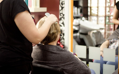 Hairdresser brushing a clients hair
