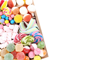 Sweet candies and lollipops in basket on white background
