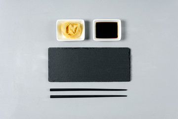 Empty black slate plate with chopstick on gray wooden background. Flat Lay. Top view. Food concept