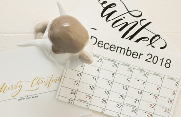 Top view: image of a praying cute angel is on background of the December 2018 calendar with holiday dates. Concept: Merry Christmas and Happy New Year are winter favorite holidays.