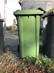 Single green trash can in front of a house