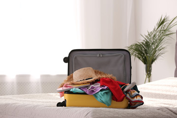 Fototapeta Modern suitcase full of clothes on bed indoors. Space for text obraz