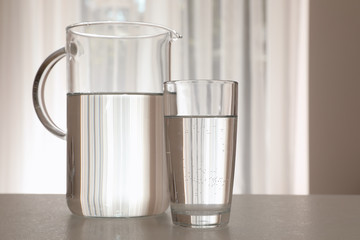 Jug and glass with water on table indoors