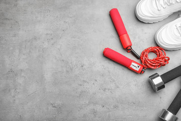 Flat lay composition with jump rope, gym equipment and space for text on grey background