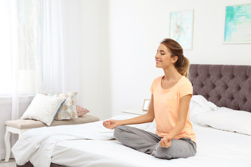 Young beautiful woman meditating on bed at home. Morning fitness