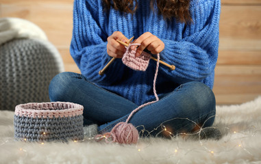 Woman in warm sweater knitting on fluffy rug at home