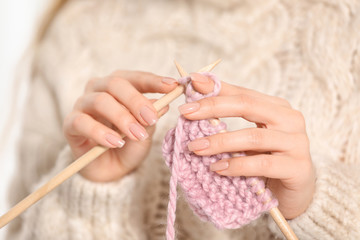 Young woman in cozy warm sweater knitting with needles, closeup