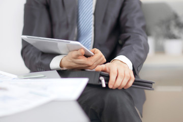 close up.Businessman with leather briefcase with digital tablet