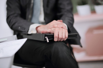 close up.A businessman with a leather briefcase sitting in an of