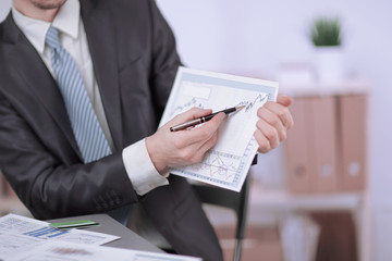 close up.Businessman pointing pencil on financial graph