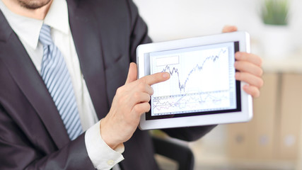 close up.Businessman pointing to a tablet with financial graph