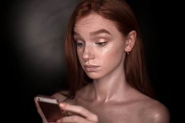 Shocked serios redhead girl woman with healthy glow wet skin posing isolated over black wall background looking aside using mobile phone chatting near empty copyspace.
